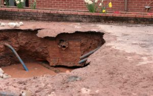 Sewer drops into sinkhole